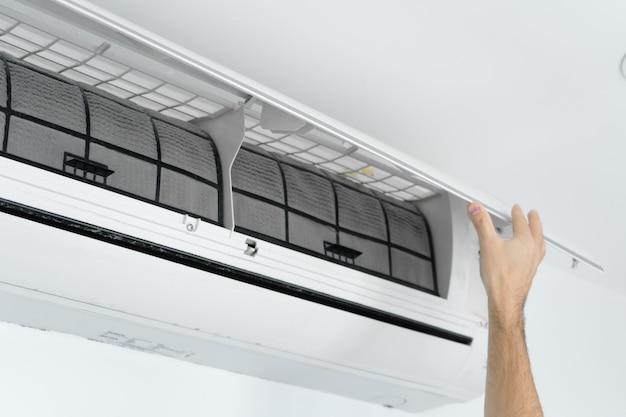 男は家庭用エアコンのフィルターをほこりから掃除します。非常に汚れたエアコンフィルター。気候設備のケア。