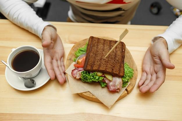 カフェの男は彼の注文サンドイッチとコーヒーを取る