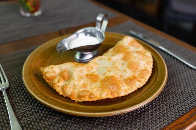 Сочный чебурек со сметаной. крымскотатарская кухня. мясной пирог.
