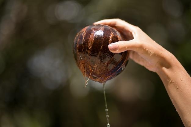 女性の手が水からココナッツを引き出した。ジャングルの緑の背景。