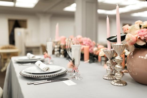 レストランの白いテーブルには生花が飾られています。スタイリッシュなイベント装飾