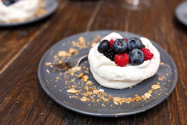 Сладкие пирожные с летними ягодами на деревянном столе. вечеринка, сладкий столик. летнее предложение десертов в ресторане.