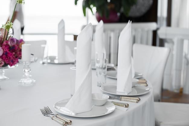 クローズアップの白いナプキンは、レストランで提供テーブルの白い皿に立つ