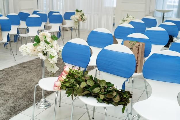 結婚式のための明るい部屋。青い布で飾られたゲストチェアの列