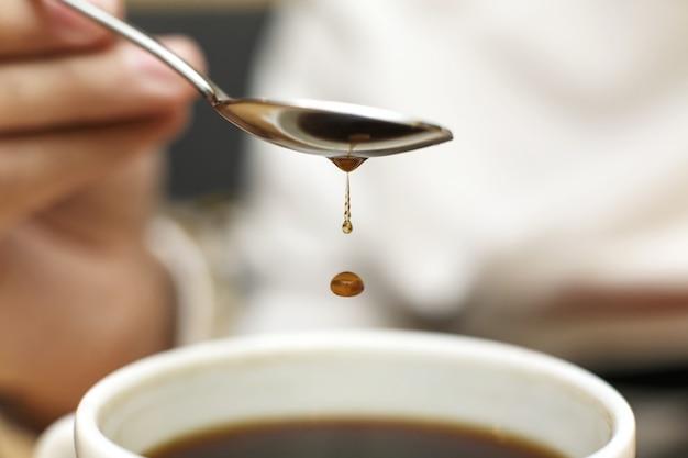 コーヒーとマグカップに金属のスプーンから滴り落ちるコーヒーのクローズアップブロブ