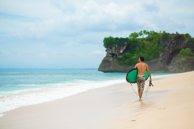 サーファー。熱帯の砂浜の上を歩いてサーフボードでサーフィン男。健康的なライフスタイル、ウォーターアクティビティ、ウォータースポーツ。美しい海。