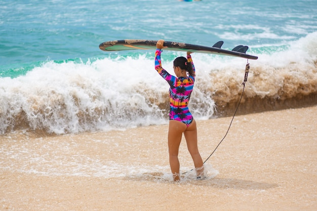 熱帯の砂浜にサーフィンボードを持つセクシーなスリムな女の子。夏の職業で健康的なアクティブなライフスタイル