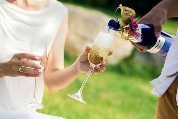 Молодожены разливают вино в бокалы.