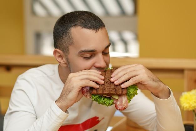 レストランで空腹の若い男がサンドイッチを食べる