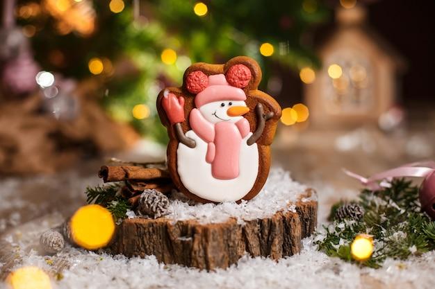 休日の伝統的な食べ物ベーカリー。ガーランドライトと居心地の良い装飾の帽子とスカーフのジンジャーブレッド幸せな雪だるま