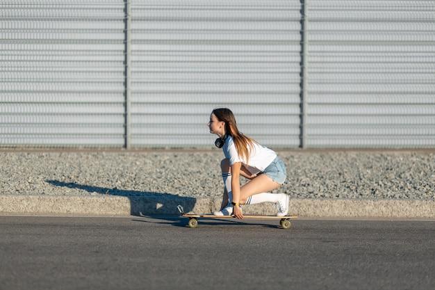 白いストッキングのスタイリッシュな女の子が通りを下ってロングボードに乗って音楽を聴く