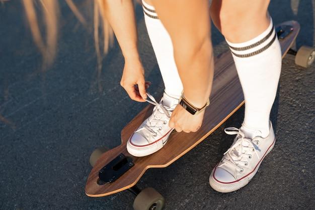 極端な面白い彼女の木製のロングボードスケートボードに乗った後休んで白いスニーカーで女性の脚のクローズアップ。現代の都市の流行に敏感な女の子は楽しい時を過します。スケートボードに最適な晴れた夏の日