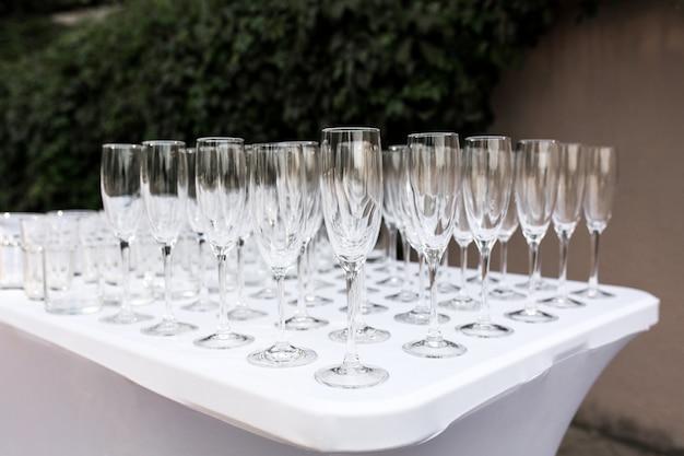 ビュッフェ式の結婚式のテーブルでゲストのための多くの空のきれいなメガネ