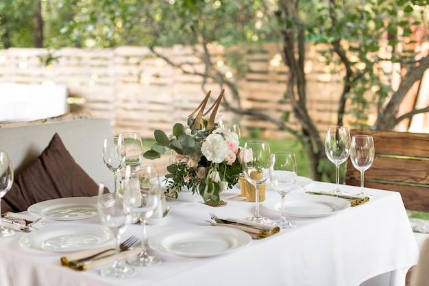 Сервировка свадебного стола украшена живыми цветами в латунной вазе. свадебная флористика. банкетный стол для гостей на свежем воздухе с видом на зеленую природу. букет с розами, эустомой и листьями эвкалипта