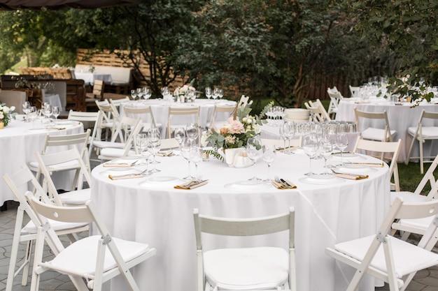 真ちゅう製の花瓶に生花で飾られた結婚式のテーブルセッティング。結婚式のフローリストリー。緑の自然の景色を望む屋外のゲスト用の宴会テーブル。バラ、トルコギキョウ、ユーカリの葉の花束
