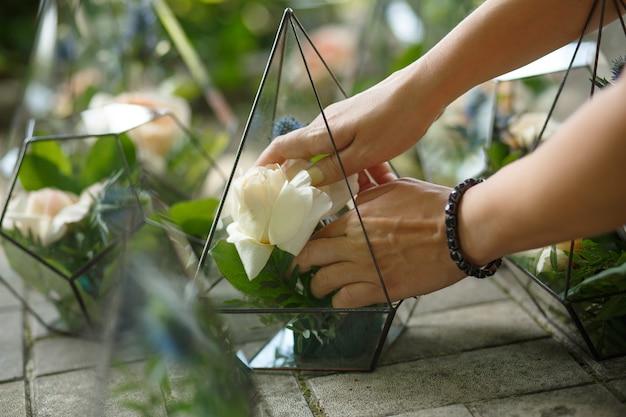 Флорариум со свежими сочными и розовыми цветами. событие украшение живыми цветами. флорист рабочий процесс. свадебный банкет