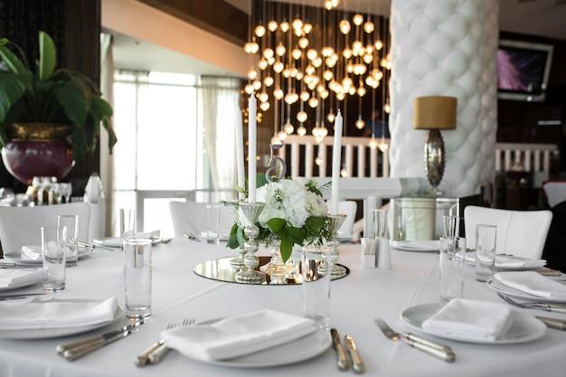 結婚式のテーブルセッティングは、新鮮な花と白いキャンドルで飾られています。結婚式のフローリストリー。バラの花束