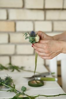 Женщина флористом руки собирает цветы для бутоньерки жениха. событие украшение живыми цветами. флорист рабочий процесс. свадебный банкет