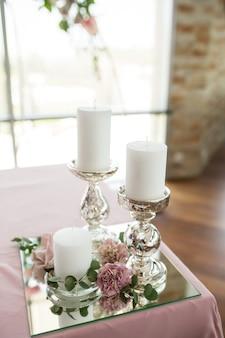新婚夫婦のための結婚式のテーブルセッティングは、カーネーション、バラ、アンスリウム、ユーカリの葉の新鮮な花で飾られています。銀の燭台、白いろうそく。結婚式のフローリストリー。クローズアップの詳細