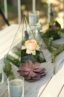 Флорариум со свежими сочными и розовыми цветами, украшение праздничного стола. событие украшение живыми цветами. флорист рабочий процесс. свадебная церемония