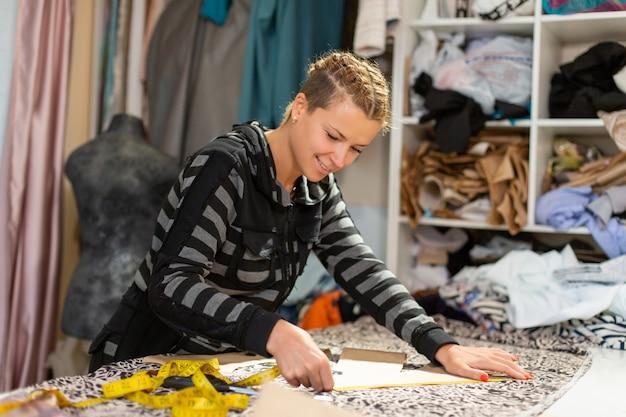 服の若い女の子のデザイナー。衣服を作るための生地のセンチメートルカットラインによる測定