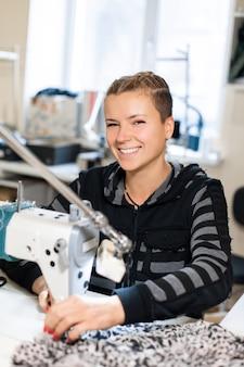 マシンでミシン仕立て屋の肖像画。職場での女性のテーラーステッチ素材