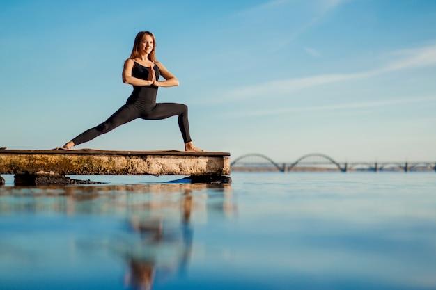 市と静かな木製の桟橋でヨガの練習の若い女性