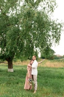 若いカップルを抱き締めると芝生の緑の草の上で踊って