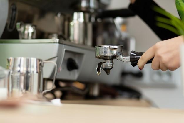 バリスタの女の子はコーヒーマシンで香り豊かなコーヒーを準備しています
