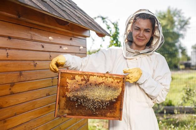 Молодой пчеловод держит деревянную раму с сотами
