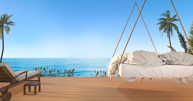 夏にハワイの素敵な空の景色とヤシの木とビーチと海の近くのテラスの美しいハンギングベッド