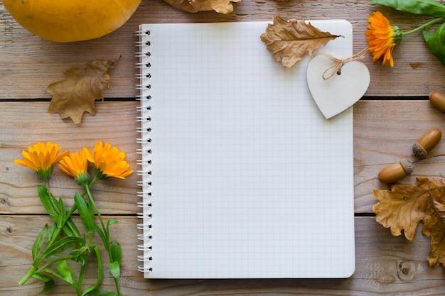 カボチャと木製の秋のテーブル上のノートブック、花の乾燥した葉