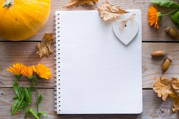 Блокнот на деревянном осеннем столе с тыквой, цветами сухими листьями