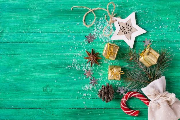 クリスマスの背景、エメラルドの木製机の上の装飾、フラットレイアウトスタイル