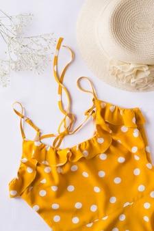 Желтое платье с белым в горошек, шапка и гипсофила на белом