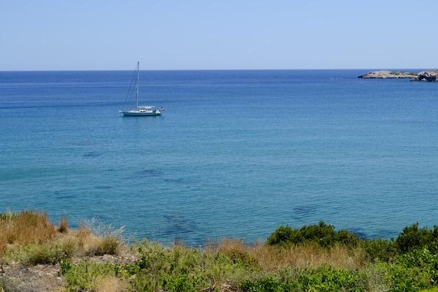 Лодка далеко на синем море и линии горизонта