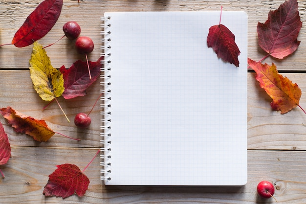 Блокнот на деревянном осеннем столе с сухими листьями и красными яблоками