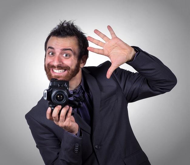 Улыбающийся бизнесмен использует свою профессиональную камеру, чтобы сделать селфи