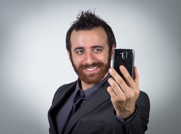 Улыбающийся бизнесмен использует свой смартфон, чтобы сделать селфи