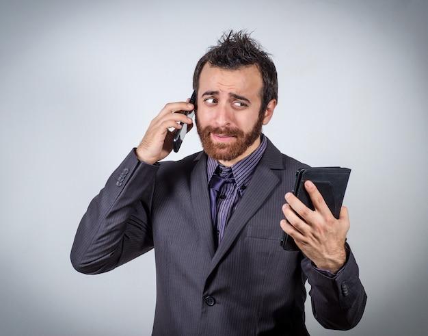 彼のスマートフォンで話していると見ている実業家彼のタブレットを困惑させた