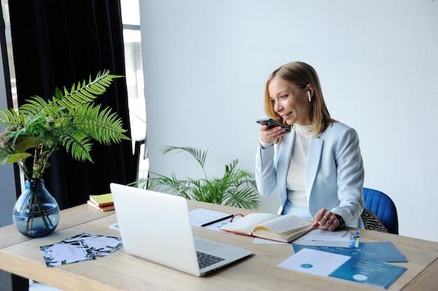 Женщина топ-менеджер диктует голосовое сообщение