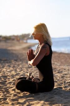 ビーチでヨガのアーサナをしている女性