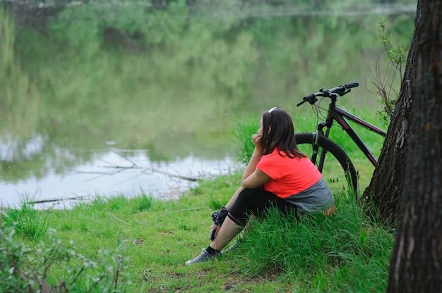Девушка отдыхает после езды на велосипеде возле дерева