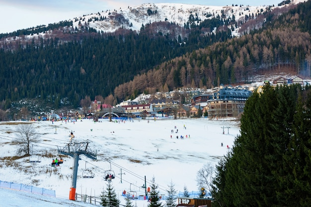 素敵な冬の日のスキーリゾート。スキーヤーとスノーボーダーがスキー場をスキーリフトのベースまで滑り降ります。木と山