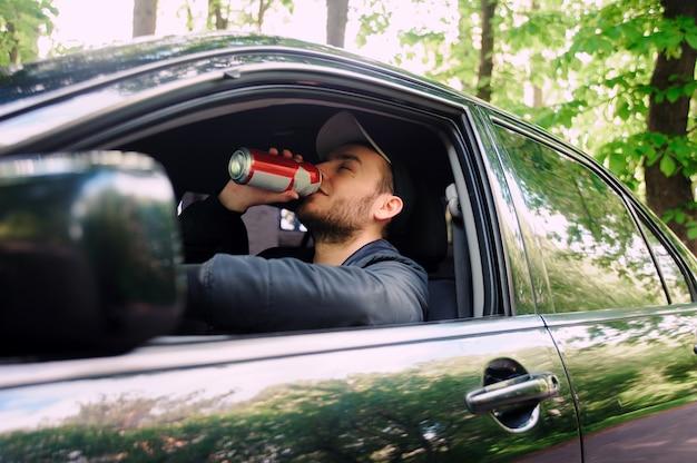 Мужчина пьет пиво во время вождения автомобиля