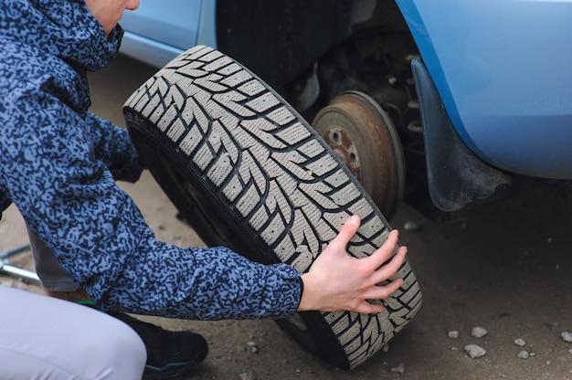 男は車のホイールでタイヤを交換しています