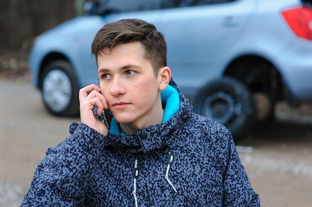男が車の車輪をたたき、テクニカルサービスに電話します