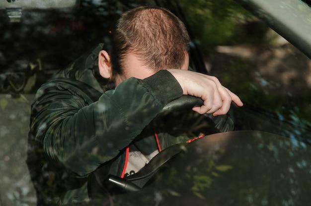 若い男が車の中で眠りに落ちる