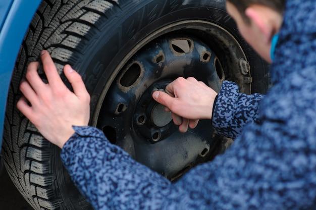 男が車の車輪を壊し、道路で自分で交換します。