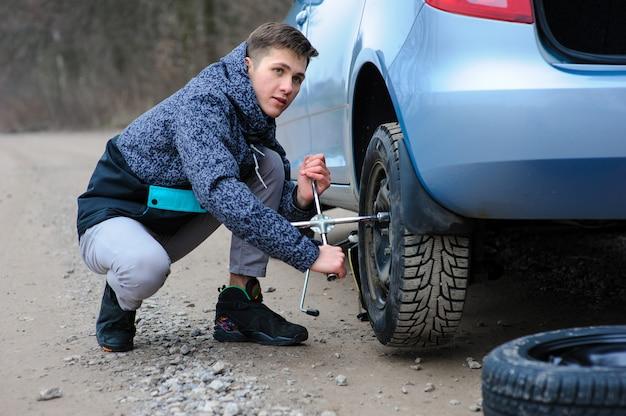 Мужчина разбил колесо на машине и самостоятельно меняет его на дороге.